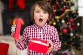 Surprised little boy holding a gift — Stock Photo