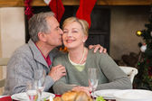 Mature man kissing the cheek of his wife — Stockfoto
