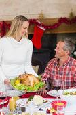 Woman serving roast turkey to her husband — Stock Photo