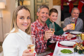 Smiling family toasting to camera during christmas dinner — Stock Photo