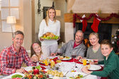 Woman holding turkey roast with family at dining table — Foto Stock