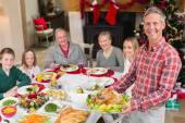 Man holding turkey roast with family at dining table — Foto Stock