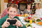 Young boy holding smartphone during christmas dinner — Stok fotoğraf