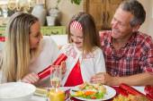 Little girl pulling a christmas cracker with their parents — Stockfoto