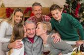 Multigeneration family with little girl kissing her grandfather — Stock Photo