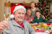 Smiling grandfather in santa hat toasting with champagne — Stock Photo