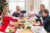 Family pulling christmas crackers at the dinner table — Stock Photo