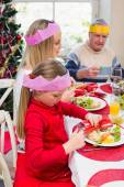 Little girl in party hat holding christmas crackers — Stock Photo