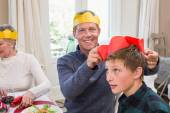 Smiling father putting party hat on sons head — Стоковое фото