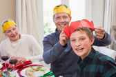 Smiling father putting party hat on sons head — Stockfoto