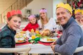 Smiling extended family in party hat at dinner table — Stock Photo