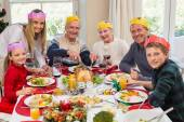 Grandfather in party hat carving chicken during dinner — Stock Photo