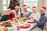 Smiling family in santa hat toasting to camera — Stock Photo