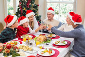Multi generation family in santa hat toasting each other — Stock Photo