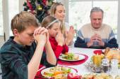 Extended family saying grace before christmas dinner — Stock Photo