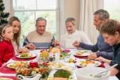 Extended family saying grace before christmas dinner — Stockfoto