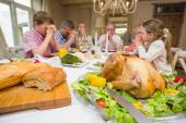 Family saying grace before christmas dinner together — Stockfoto