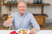 Smiling man toasting at christmas dinner — Stock Photo
