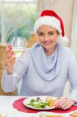 Pretty young woman in santa hat toasting with white wine — Stock Photo