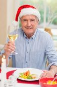 Smiling mature man in santa hat toasting with white wine — Stock Photo