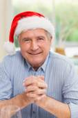 Portrait of mature man in santa hat with hands together — Stockfoto