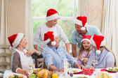 Happy extended family in santa hat speaking together — Stock Photo