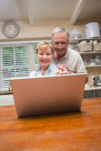Senior couple using the laptop together — Stock Photo