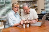 Senior couple looking up medication online — Stock Photo