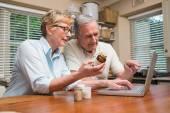 Senior couple looking up medication online — Stock Photo