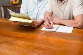Senior couple reading and writing — Stock Photo