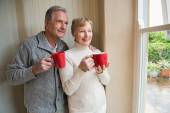 Senior couple holding red mugs — Stock Photo