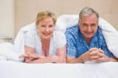 Senior couple smiling under the duvet — Stock Photo