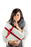 Brunette holding gift and keeping a secret — Stock Photo