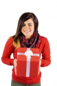Smiling brunette showing a gift with white bow — Stock Photo