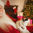 Father christmas holding engagement ring with his box — Stock Photo #60840419