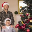 Dad and son posing near the christmas tree — Stock Photo #60842383