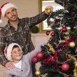 Smiling son and dad decorating the christmas tree — Stock Photo #60842403