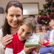 Daughter holding a gift with her mother — Stock Photo #60842787