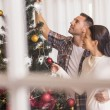 Love couple decorating the christmas tree together — Stock Photo #60843035
