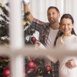 Smiling couple decorating the christmas tree together — Stock Photo #60843041