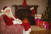 Festive santa claus sitting on couch at christmas — 图库照片