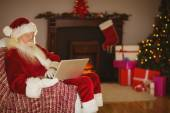 Santa using laptop on the couch at christmas — 图库照片