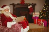 Santa using laptop on the couch at christmas — Stock Photo