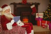 Santa using tablet on the couch at christmas — 图库照片