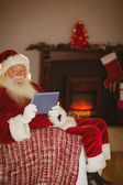 Smiling santa using tablet on the couch  — Stockfoto