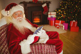 Happy santa using tablet on the couch  — Stock Photo