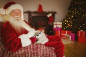Happy santa touching tablet on the couch — Stock fotografie