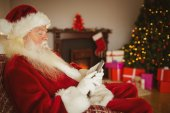 Concentrated santa using smartphone at christmas — Stock Photo