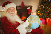 Smiling santa pointing his finger on the globe — 图库照片