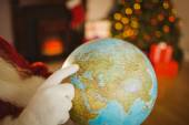 Close up of santa pointing his finger on the globe — 图库照片